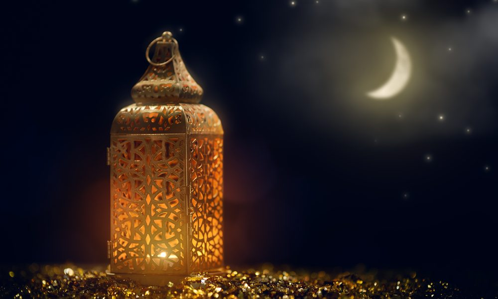 Ornamental Arabic lantern with burning candle glowing at night, representing Muslim holy month Ramadan.